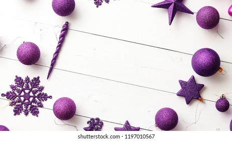 Christmas purple collection, balls and decorative ornaments, on white wooden background. Circle shaped with copy space.