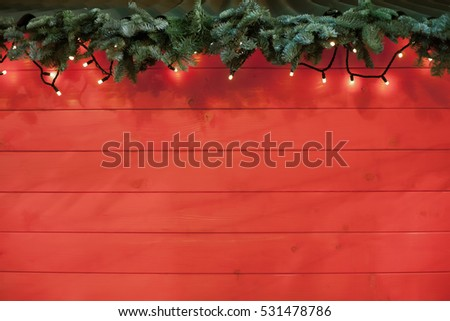 christmas red backgroundrustic new year tree branch with lights on red wooden back