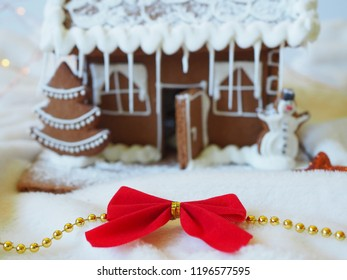 Christmas red bow in front of a gingerbread house in the background