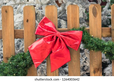 Christmas red bow on a wooden fence with green vegetation.