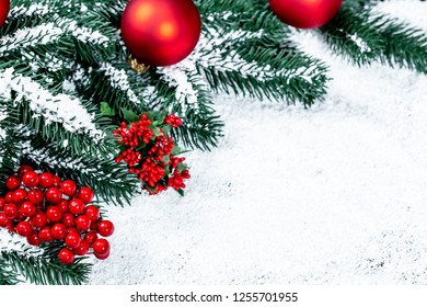 Christmas red decor and balls with Christmas tree branches on snow. Beautiful New year background