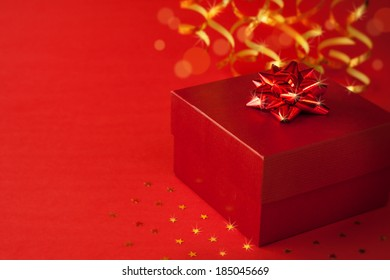 Christmas red gift box with glossy ribbon - background with free text space.