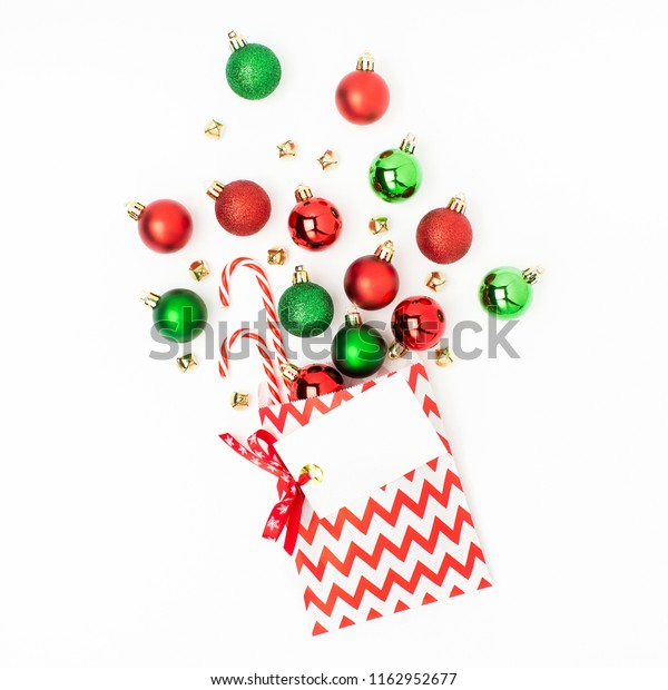 Christmas red and green balls  flowing from a gift bag on white background Flat lay, top view trendy holiday concept.