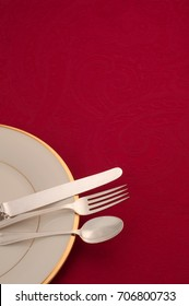 Christmas Red Place Setting in bottom corner with Silver Ware, Cream White China Plate on Textured Table Cloth with room or space above for copy, text, or your words.  It's vertical and flat lay view