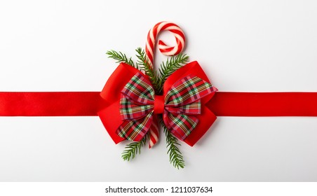Christmas red ribbon with bow and candy cone on white background. Top view. Christmas decor for gift box.