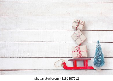 Christmas red sled carried gift box, spruce on white wooden table, vintage style, top view, new year composition,
