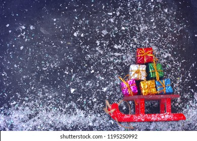 Christmas red sled carry bunch of colorful gift box, on black surface, snowfall, vintage style, new year composition