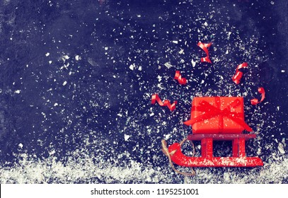 Christmas red sledges carry gift box, serpentine on black surface, snowfall, vintage style, new year night composition