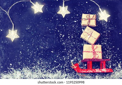 Christmas red sleigh carrying bunch gift box, light garland star on black surface, vintage style, new year night composition