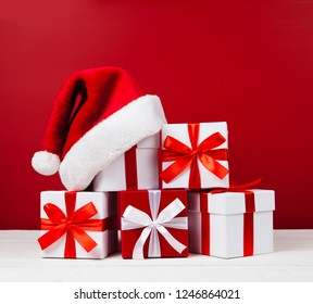 Christmas red and white gift boxes in the shape of a pyramid with Santa hat on top on red background