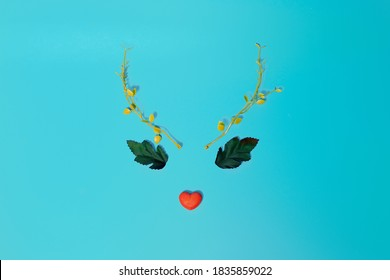 Christmas reindeer art design made od green leafs red heart and antler of branches on blue background. Minimal idea for holiday. Flat lay design