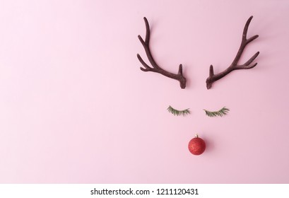 Christmas reindeer concept made of evergreen fir, red bauble decoration and antlers on pastel pink background. Minimal winter holidays idea. Flat lay top view composition.