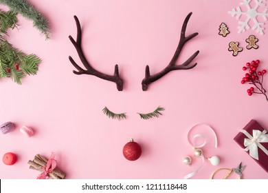 Christmas reindeer concept with presents, decoration, and winter things on pastel pink background. Minimal winter holidays idea. Flat lay top view composition.