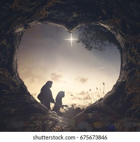 Christmas religious nativity story concept: Silhouette mother Mary and father Joseph looking Jesus born in birth manger with heart shape of tomb stone on night