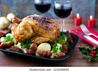 Christmas Roasted Cooked Turkey Dinner with trimmings pigs in blankets potatoes herbs wine glasses candles and holly.