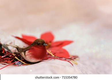 Christmas robin with red flowers and tinsel on a cream background