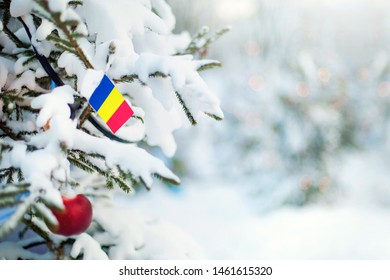 Christmas Romania. Xmas tree covered with snow, decorations and a flag of Romania. Snowy forest background in winter. Christmas greeting card.