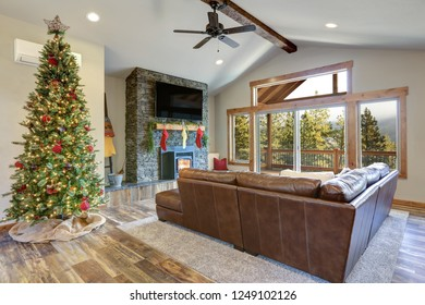 Christmas room interior design. Living space features beamed ceiling, stone fireplace and decorated Christmas tree.