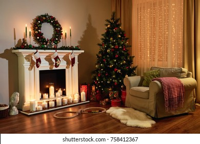 Christmas room interior design, Xmas tree decorated dy lights presents gifts toys, candles and garland lighting indoors fireplace. Christmas holiday living room. New year design.