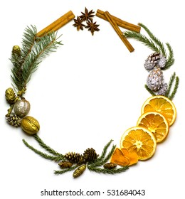 Christmas round frame from fir tree branch, golden and silver pine cones, walnuts, cinnamon. star anise, dry oranges fruit. Flat lay. New Year`s background isolated on white.