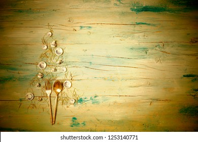 Christmas rustic menu dinner background. Christmas tree made with plates, cups and cutlery with a blank wooden table background