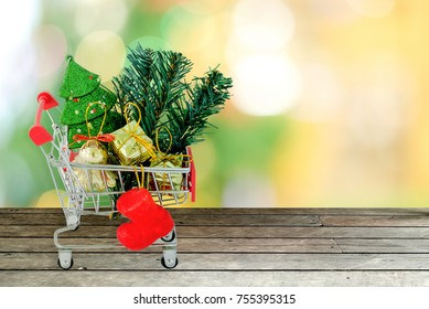 Christmas sale and shopping lists. Shopping cart trolley carrying Cristmas decorative items, ornaments, gift box, tree and red sock on vintage wood plank.table top over blurred Christmas background