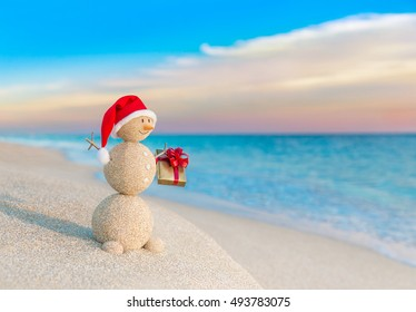 Christmas Sandy Snowman in red Santa Claus hat with holiday gift box at ocean sunset beach. New Year's vacation discounts in hot countries concept