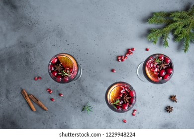 Christmas sangria with oranges, pomegranate seeds, cranberry, rosemary and spices - homemade festive drink mulled wine for Christmas time.