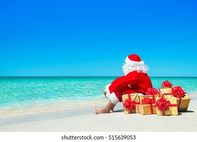 Christmas Santa Claus with golden gift fancy boxes relaxing at ocean tropical beach sand - New Year travel destinations vacation in hot countries travel price discounts concept