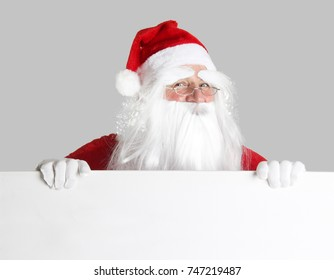 Christmas Santa Claus holding a blank white poster. Add your own text.