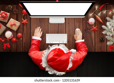 Christmas in Santa Claus home. Santa Claus use a computer to respond to letters from children around the world.
