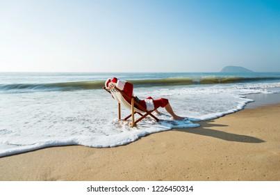 Christmas santa claus lying on a beach chair.