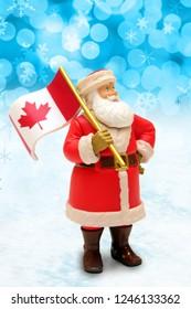 Christmas Santa Claus ornament holding a Canada maple leaf flag.