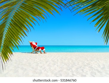 Christmas Santa Claus relaxing on sunlounger at ocean sandy tropical beach under palm leaves. Happy New Year travel destinations to hot countries concept
