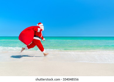 Christmas Santa Claus running with big sack full of gifts hurry on present for children along ocean tropical sandy beach - xmas travel vacation discounts and travel agencies price reductions concept
