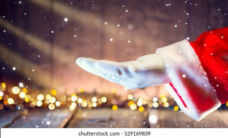 Christmas Santa Claus showing empty copy space on the open hand palm for text. Proposing product. Advertisement gesture presenting point. Holding gift, text or product over wooden background.