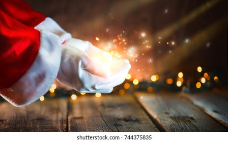 Christmas Santa Claus showing magic in open hands palm.Glowing stars and magic dust. Proposing product. Advertisement gesture presenting point. Holding gift, text or product over wooden background.