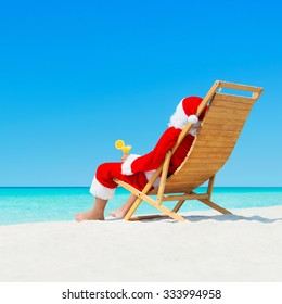 Christmas Santa Claus sunbathing on sunlounger with fresh orange juice cocktail at ocean tropical beach - xmas travel vacation in hot countries concept