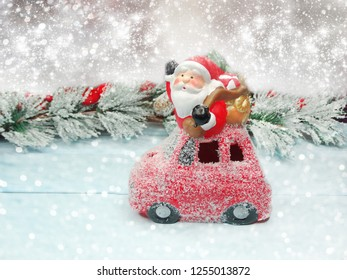 christmas santa with fir tree branch cones and snow on background with garland lights