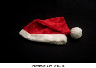 A Christmas Santa hat on a black canvas cloth
