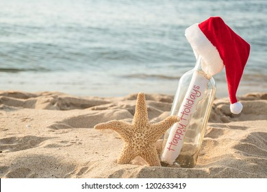 Christmas Santa hat on Happy Holidays message in a bottle with starfish in beach sand and water background