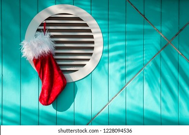 Christmas Santa stocking hanging from brightly colored Caribbean blue wall with tropical palm tree shadows