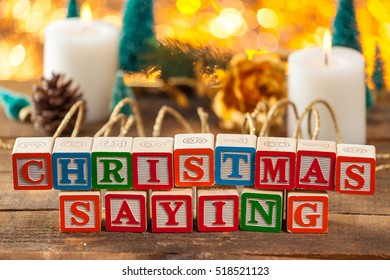 Christmas Saying Written With Toy Blocks On Holiday Card Background With Copy Space.