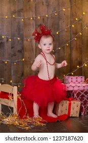Christmas scene of baby girl posing with presents in studio shoot. Happy smile child celebrating new year holiday