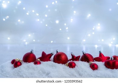 Christmas scene with snow - red balls decorations row, lights in background
