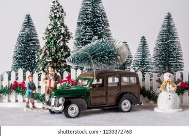 Christmas scene with toy woodys station wagon on snow in front of white picket fence with snow man and father daughter next to car and white background