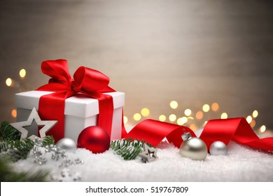 Christmas scene with a white gift box, red bow and ribbon, lights, baubles, fir branches and snow, with copy space