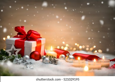 Christmas scene with a white gift box, red bow and ribbon, candles, lights, baubles, fir branches and snow, with copy space