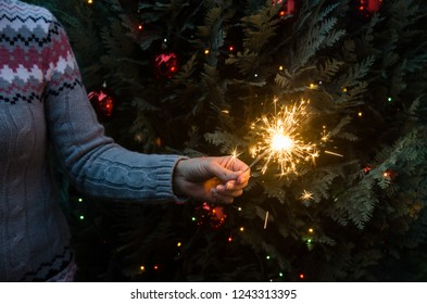 Christmas scene - woman in knitted winter sweater holding sparklers before the decorated christmas tree