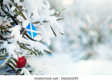 Christmas Scotland. Xmas tree covered with snow, decorations and a flag of Scotland. Snowy forest background in winter. Christmas greeting card.